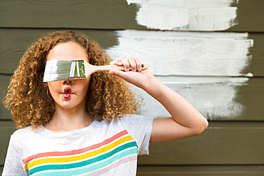 Girl covering her eyes with paint brush