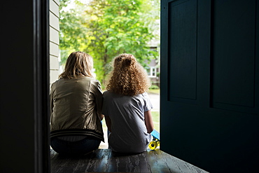 Mother and daughter sitting on porch