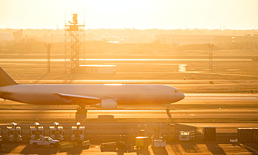 Airplane on runway at sunset