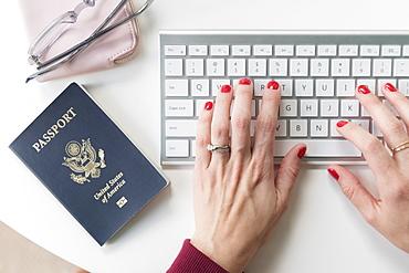 Woman typing on keyboard by passport