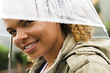 Smiling woman under wet umbrella