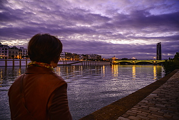 Woman by Guadalquivir river at sunset in Seville, Spain