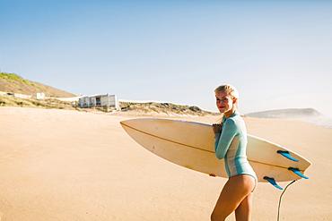 Woman wearing wetsuit holding surfboard on beach