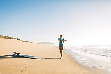 Woman wearing wetsuit stretching on beach