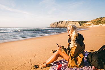 Woman holding phone sitting on beach