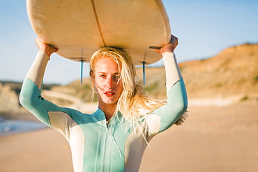 Woman holding surfboard above her head at beach