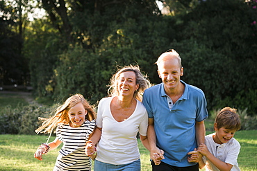 Family smiling and holding hands by trees