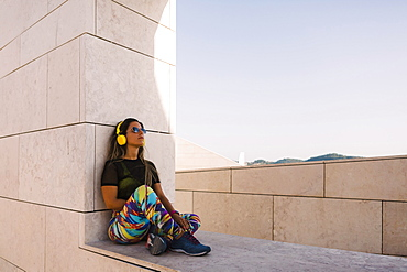 Woman wearing headphones sitting on wall