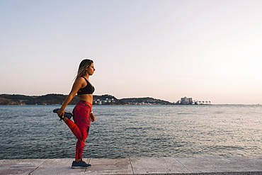 Woman stretching by sea, Lisboa, Lisbon, Portugal