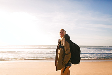 Woman wearing backpack at beach