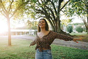 Smiling woman with her arms outstretched in park, Lisboa, Lisbon, Portugal