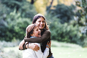 Smiling sisters embracing by bush