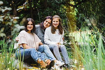 Mother and daughters embracing on grass