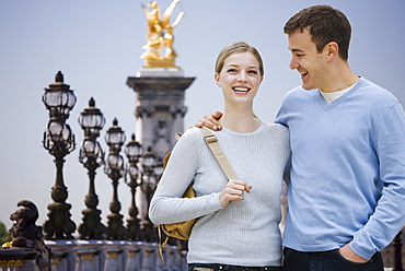 Couple smiling with golden statue in background