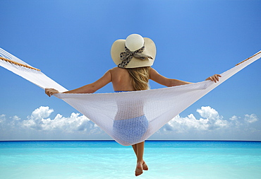 Rear view of woman sitting in hammock at beach