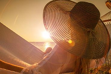 Woman wearing hat on hammock at sunset