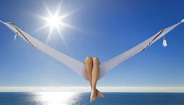 Woman's legs hanging over side of hammock at beach