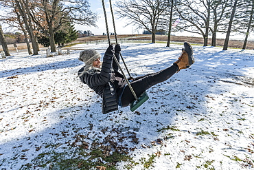 Woman on swing in snow, Mount Horeb, Wisconsin, USA