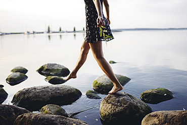 Barefoot woman stepping on rocks in sea