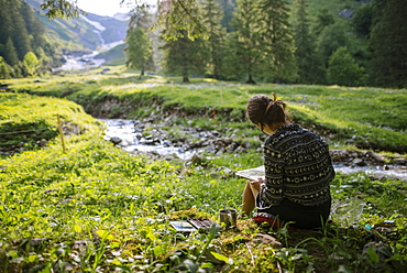 Woman painting with watercolors by river in Appenzell, Switzerland
