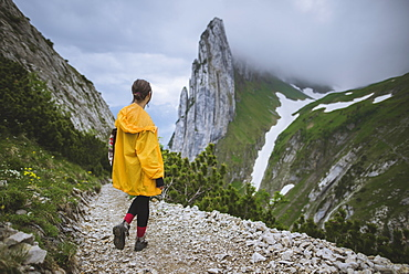 Woman wearing yellow jacket by mountains in Appenzell, Switzerland