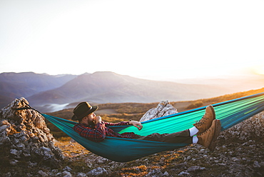 Man lying on hammock in mountain range