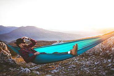 Man sleeping on hammock in mountain range