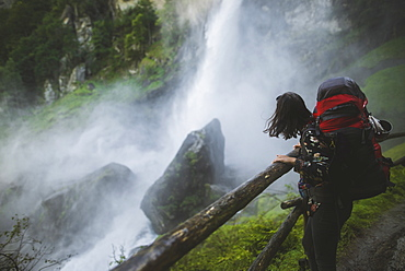 Woman wearing backpack by waterfall