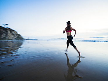 Woman wearing sports clothes running on beach