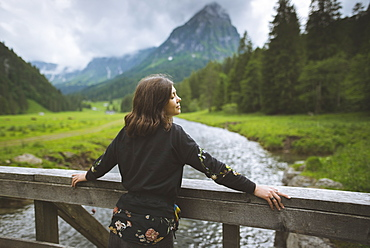 Young woman leaning on railing by river