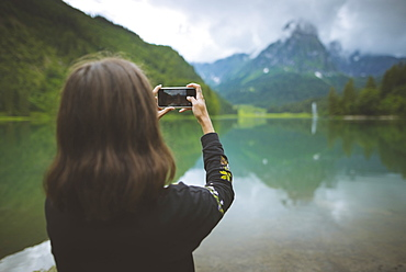 Young woman photographing mountain and lake with smartphone