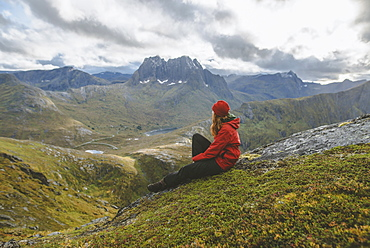 Young woman in red jacket sitting on mountain