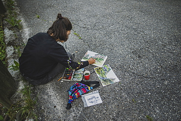 Young woman painting mountains on road