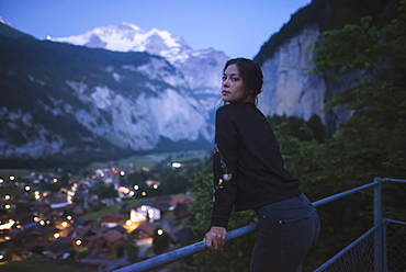 Young woman leaning on railing by mountain and village