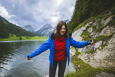 Smiling young woman in blue jacket by lake