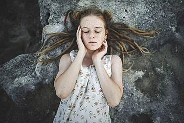 Young woman with dreadlocks lying on rock