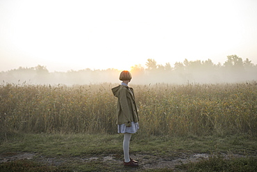 Young woman by field of long grass at sunset