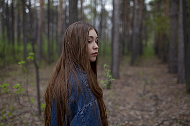 Young woman with denim jacket in forest