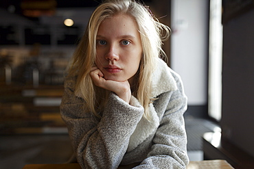 Young woman with wool coat in cafe