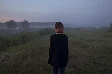 Rear view of young woman in field at sunset