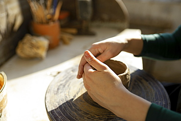 Hands of woman molding clay on potter's wheel