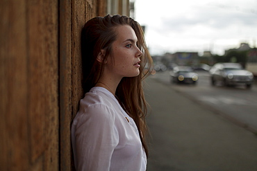 Young woman leaning on wooden fence in city