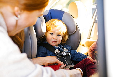 Boy having his seat belt buckled by his mother