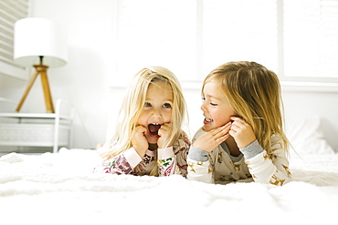 Sisters lying on bed