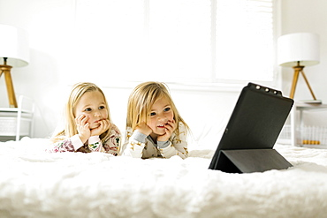 Girls watching movie on digital tablet while lying on bed