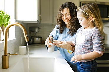 Mother and daughter washing hands in kitchen sink