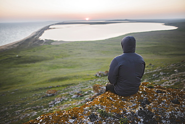 Young man in hooded jacket sitting on hill during sunset