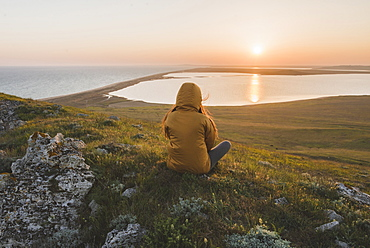 Woman in hooded jacket sitting on hill during sunset