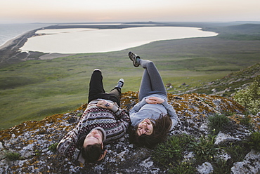 Young couple lying on hill at sunset