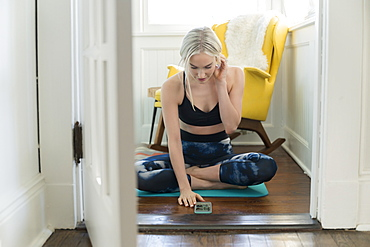 Woman working out at home with live stream on phone